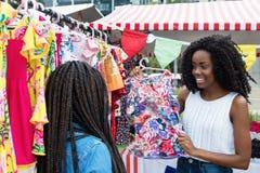 当前五颜六色的衣裳的非裔美国人的妇女在市场上 图库摄影