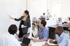 当前会议的妇女在一whiteboard在一个繁忙的办公室 图库摄影