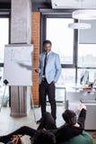 当前办公室会议的年轻黑人在活动挂图 免版税图库摄影
