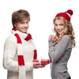 当前圣诞节礼品的逗人喜爱的人对妇女 库存照片