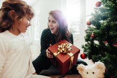 当前圣诞节礼物的母亲对女儿 免版税库存照片