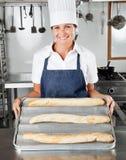 当前大面包的女性厨师在厨房里 库存照片