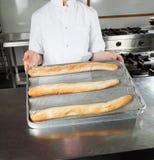 当前大面包的女性厨师在厨房里 图库摄影