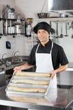 当前大面包的男性厨师在厨房里 免版税图库摄影
