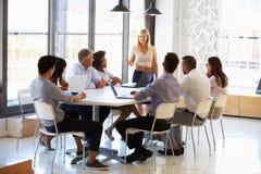 当前对同事的女实业家在会议上 免版税库存照片