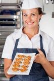当前心脏形状曲奇饼的女性厨师 库存照片