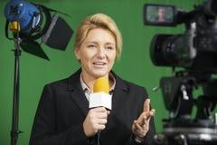 当前报告的女性新闻工作者在电视演播室 库存图片
