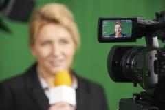 当前报告的女性新闻工作者在电视演播室 库存照片