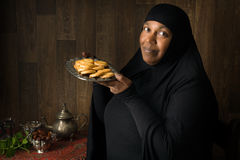 当前曲奇饼的非洲回教妇女 免版税库存照片