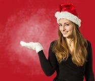 当前某事在红色backgro的开放手上的逗人喜爱的圣诞老人女孩 免版税库存图片