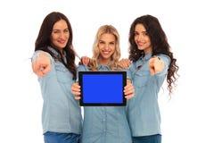 当前片剂的屏幕和指向f的三名愉快的妇女 免版税库存图片