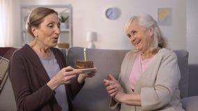 当前生日蛋糕对她的姐妹,愉快的夫人吹的蜡烛的成熟妇女 股票视频