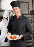 当前盘的厨师在厨房里 免版税库存图片