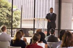 当前研讨会的黑商人微笑对观众 库存图片