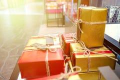 当前礼物与红金包装纸和未加工的绳索弓装饰 库存照片