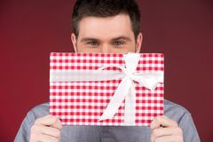 当前礼物在微笑的人覆盖物半面孔的手上 免版税库存照片