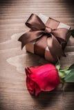 当前箱子扩展了在木板假日概念的红色玫瑰 免版税库存照片
