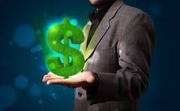 当前绿色发光的美元的符号的年轻商人 免版税库存图片