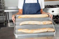 当前被烘烤的大面包的女性厨师 免版税库存图片