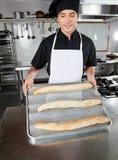 当前被烘烤的面包大面包的男性厨师 免版税图库摄影