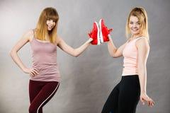 当前运动服教练员鞋子的两名妇女 免版税图库摄影