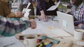 当前项目的女性经理,实施纸张文件 年轻混合的族种队业务会议  图库摄影