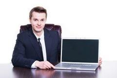 当前他在膝上型计算机的年轻愉快的成功的商人起始的项目在办公室 免版税库存照片
