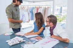 当前他的凹道的时装设计师对同事 免版税库存图片
