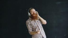 当听到在黑背景时的音乐有胡子的年轻人画象投入耳机和跳舞 免版税库存照片