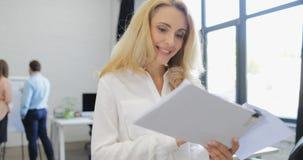 当商人合作突发的灵感谈论项目在期间时,女实业家上司读了报告文件愉快微笑 股票视频