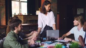 当团队负责人站立在时,年轻人和妇女工作小组在办公室谈话然后做上流五在会议期间 股票录像