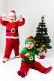 当圣诞老人和圣诞老人的帮手打扮的两个男婴在旁边 免版税图库摄影