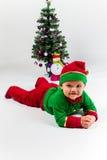 当圣诞老人的帮手打扮的男婴说谎在圣诞树旁边。 免版税库存图片