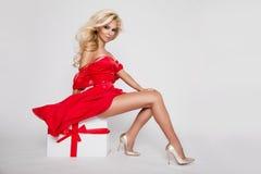 当圣诞老人色情红色女用贴身内衣裤穿戴的美丽的性感的白肤金发的女性式样雪花 免版税库存照片
