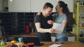 当在家时,食用早餐有吸引力的愉快的夫妇在厨房里收到好消息展开信 股票视频