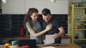 当在家时,食用早餐有吸引力的愉快的夫妇在厨房里收到好消息展开信 影视素材