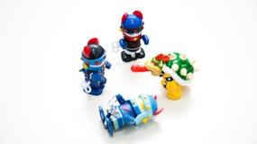 当在白色背景的一条妖怪狗由头戴一支蓝盔部队时的机器人击倒,其他两个机器人会集  库存照片