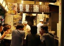 当地人民与dinning在新宿Yakitori Yokocho街道的一些个游人混合了 免版税库存照片