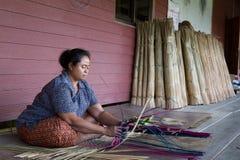 当地妇女在传统手工制造席子工作在泰国 免版税库存照片
