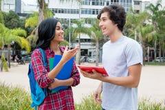 当地拉丁美洲的女学生谈话与白种人frie 库存图片