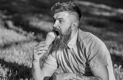 当坐草时,有长的胡子的人享用冰淇凌 纤巧概念 有冰淇凌的有胡子的人 308个黄铜弹药筒报道了遥远的空的地面下跪人步枪射击吊索雪目标冬天 免版税图库摄影