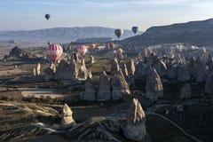 当太阳在Goreme附近在土耳其的卡帕多细亚地区升起气球在神仙的烟囱附近漂浮 免版税库存照片