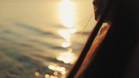 当太阳设置在水时,一个美丽的女孩通过她的头发跑她的手指 一个特写镜头 一张侧视图 股票录像
