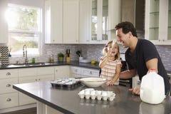当女孩在他的鼻子上把蛋糕粉放在厨房,爸爸笑 免版税库存照片