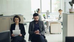 当女性经理是时,在办公室等待面试读cv和使用智能手机的被注重的候选人 影视素材