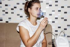当她咳嗽时,妇女在家使用一台吸入器 呼吸道疾病的治疗 与支气管炎的吸入 库存图片