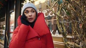 当她在冷的冬天街道上时,站立迷人的妇女看起来愉快谈话在电话 影视素材