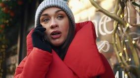 当她在冷的冬天街道上时,站立迷人的妇女看起来愉快谈话在电话 股票视频