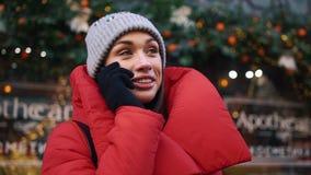 当她在冷的冬天街道上时,站立迷人的妇女看起来愉快谈话在电话 股票录像