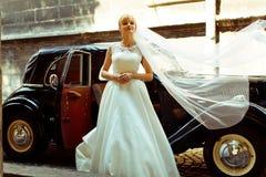 当她在它后时,站立新娘的面纱延长了一辆减速火箭的汽车 免版税库存照片